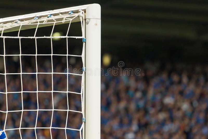 M?lstolpe med fotbollfans i bakgrunden royaltyfri fotografi