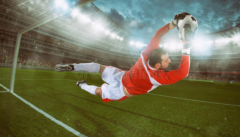 M?lvakten f?ngar bollen i stadion under en fotbolllek royaltyfri fotografi