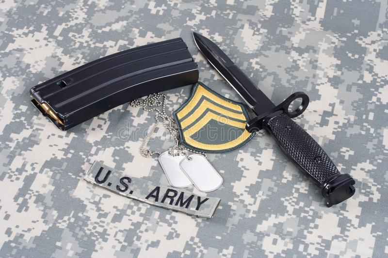 M-16 magazine with ammo and bayonet on camouflage US Army uniforms. Background stock images