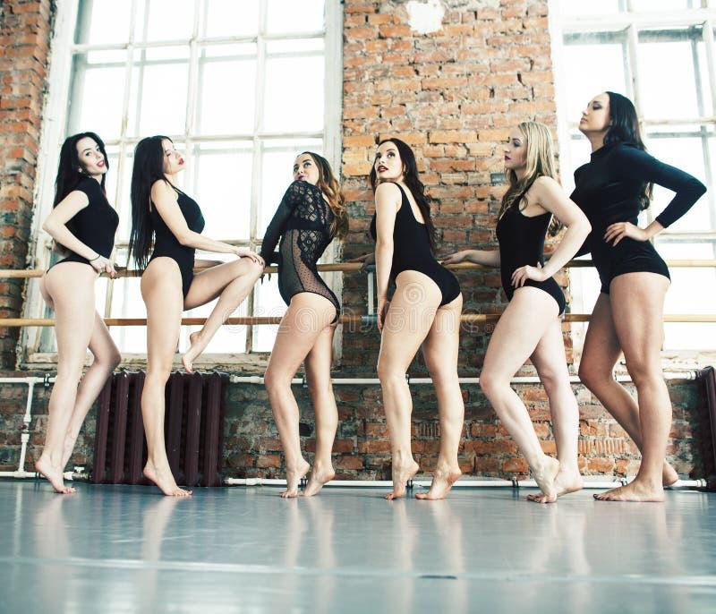 M?nga flickor som utbildar i studiobalett, den l?nga kvinnan, l?gger benen p? ryggen sexigt st?dja, den b?rande sexuella svarta b arkivfoton