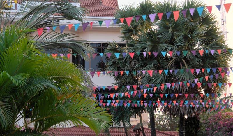M?nga m?ngf?rgade flaggor dekorerar gatan Dekorativa girlander tropiska trees arkivfoto