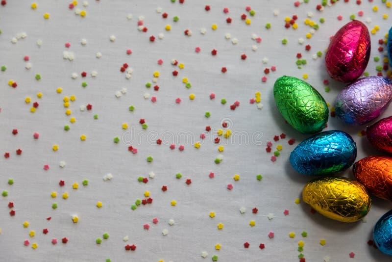 M?nga st?ende kul?ra chokladeaster ?gg p? vit bakgrund och f?rgrika konfettier arkivbilder