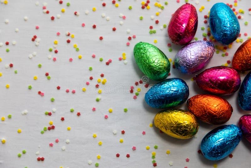 M?nga st?ende kul?ra chokladeaster ?gg p? vit bakgrund och f?rgrika konfettier fotografering för bildbyråer