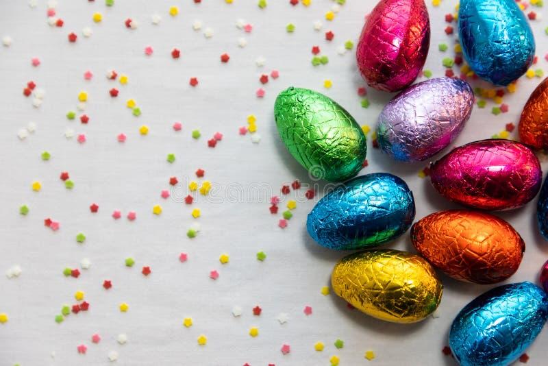 M?nga st?ende kul?ra chokladeaster ?gg p? vit bakgrund och f?rgrika konfettier royaltyfri foto