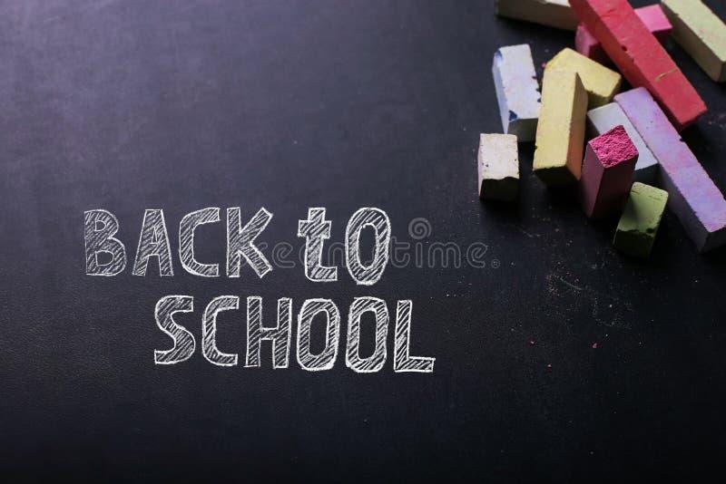 M?ngf?rgade f?rgpennor ligger p? en svart svart tavla, kopieringsutrymme Begreppet av skola, utbildning och barndom royaltyfria foton