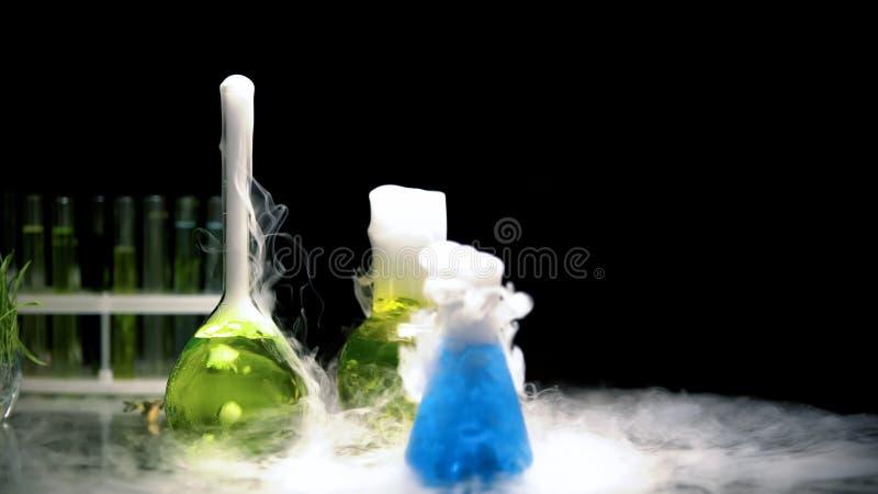 M?ngf?rgade vikter i flaskor som bubblar och s?nder ut r?k i m?rker, prov royaltyfri bild