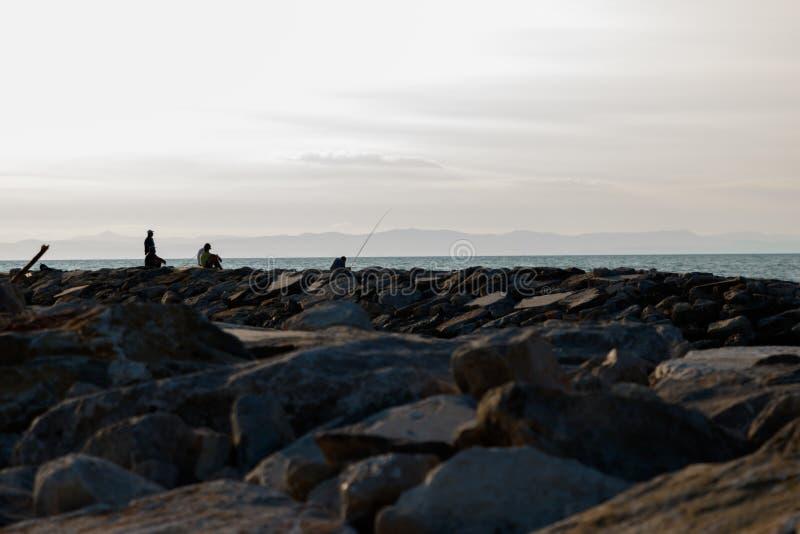 M?nner fischen von den Wellenbrechern lizenzfreies stockfoto