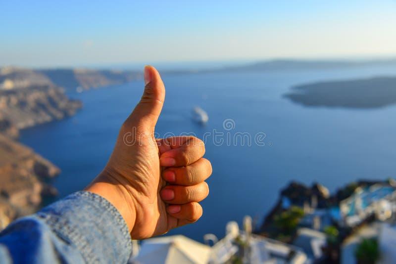 M?nnliche Hand mit Meerblick von Santorini-Insel lizenzfreie stockbilder