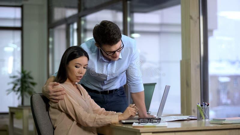 M?nnlicher Arbeitgeber, der sch?nen weiblichen Auszubildenden, Frau entsetzt durch Bel?stigung umarmt stockfoto