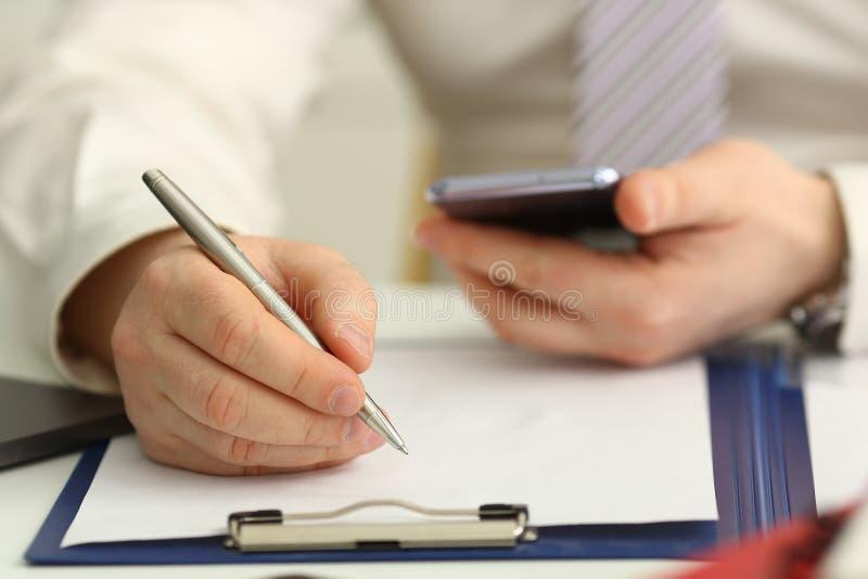 M?nnlicher Arm im Anzug und Bindung halten silbernen Stift stockbilder