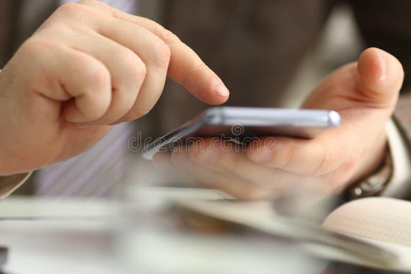 M?nnlicher Arm im Klagengrifftelefon- und -silberstift lizenzfreie stockfotografie