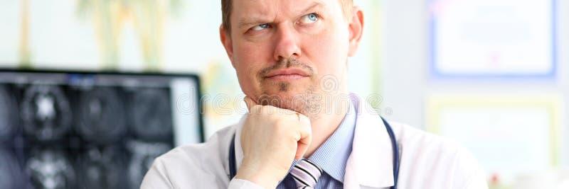 M?nnlicher Doktor mit merkw?rdigem Gesichtsausdruck in seinem B?ro sitzen lizenzfreie stockfotos