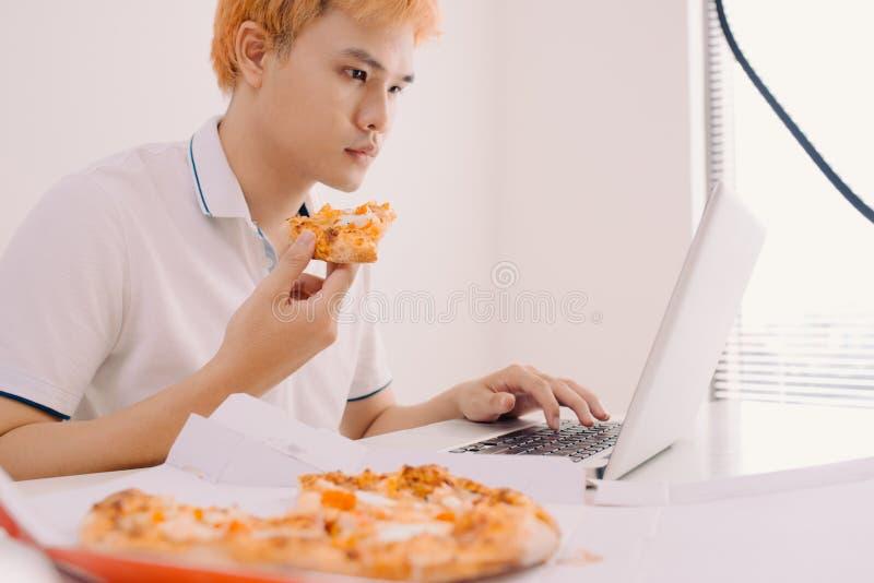 M?nnlicher Freiberufler, der Pizza beim B?ro zu Hause bearbeiten isst lizenzfreie stockbilder