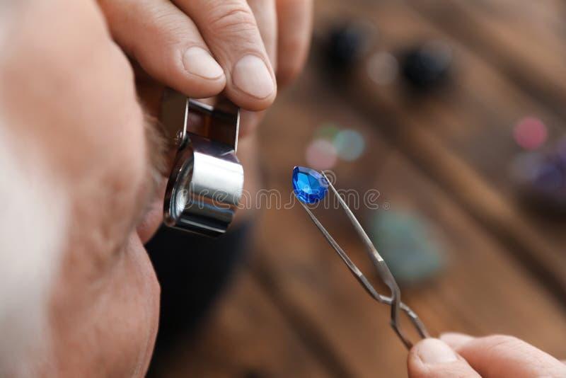 M?nnlicher Juwelier, der kostbaren Edelstein in der Werkstatt auswertet stockbild