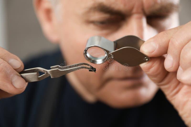 M?nnlicher Juwelier, der kostbaren Edelstein in der Werkstatt auswertet lizenzfreies stockbild