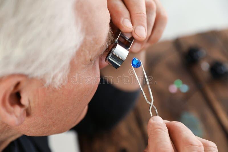 M?nnlicher Juwelier, der kostbaren Edelstein in der Werkstatt auswertet stockbilder