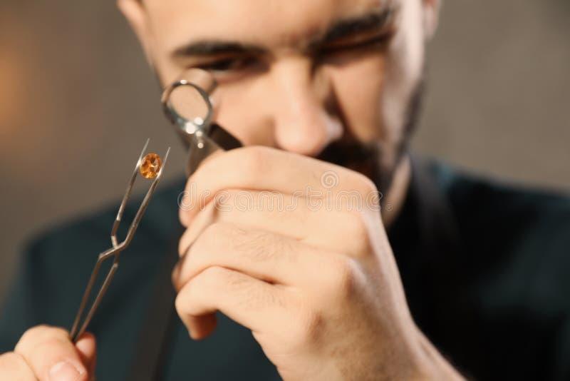 M?nnlicher Juwelier, der kostbaren Edelstein in der Werkstatt auswertet stockfotos