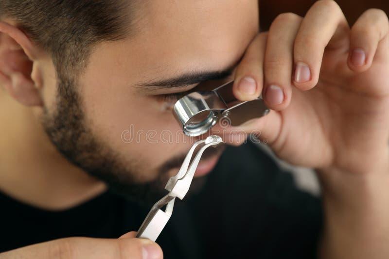 M?nnlicher Juwelier, der kostbaren Edelstein in der Werkstatt auswertet lizenzfreie stockfotografie