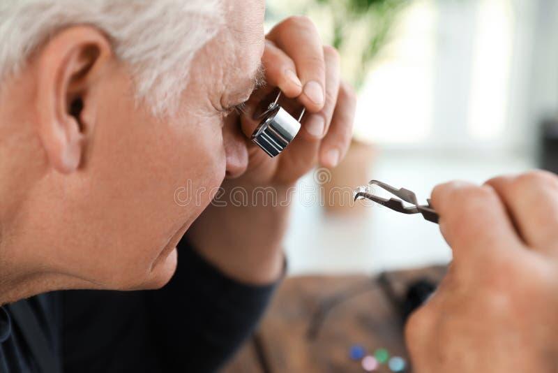 M?nnlicher Juwelier, der kostbaren Edelstein in der Werkstatt auswertet lizenzfreie stockbilder