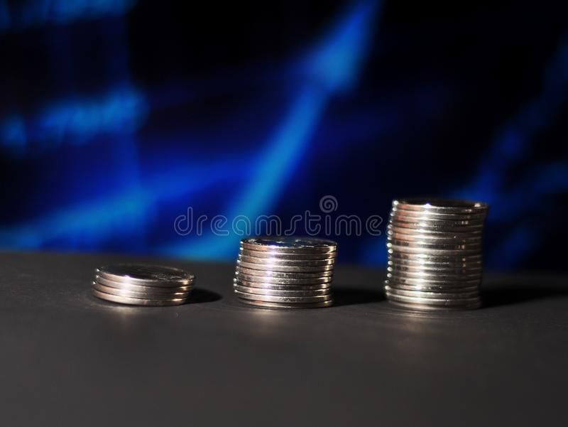 M?nzenschritte mit blauem grafischem unscharfem Hintergrund stockbild