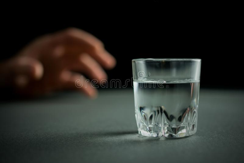 A m?o alcan?a para um vidro da bebida da vodca ou do ?lcool foto de stock royalty free