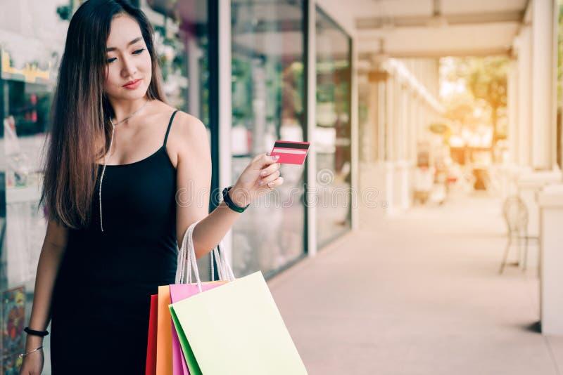 M?o ascendente pr?xima das mulheres que guardam o cart?o e os sacos de compras de cr?dito no shopping imagem de stock