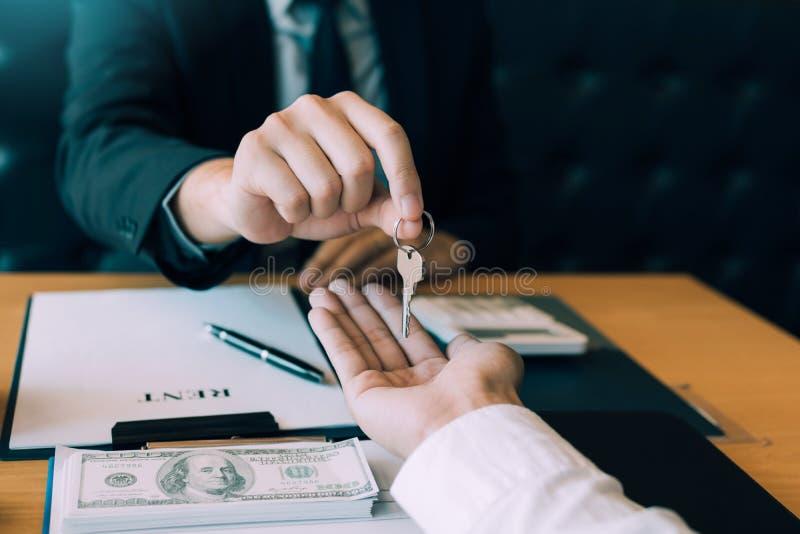 A m?o ascendente pr?xima de agentes da casa est? distribuindo chaves aos compradores de casa novos imagem de stock royalty free