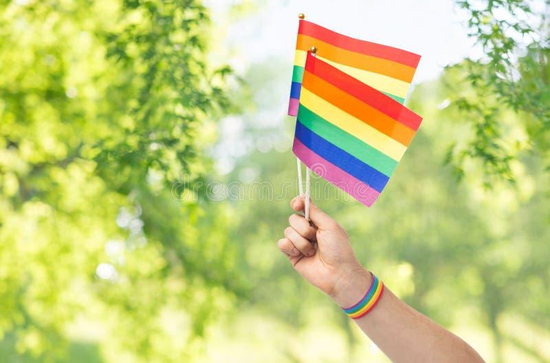 M?o com as bandeiras e o punho do arco-?ris do orgulho alegre imagens de stock royalty free
