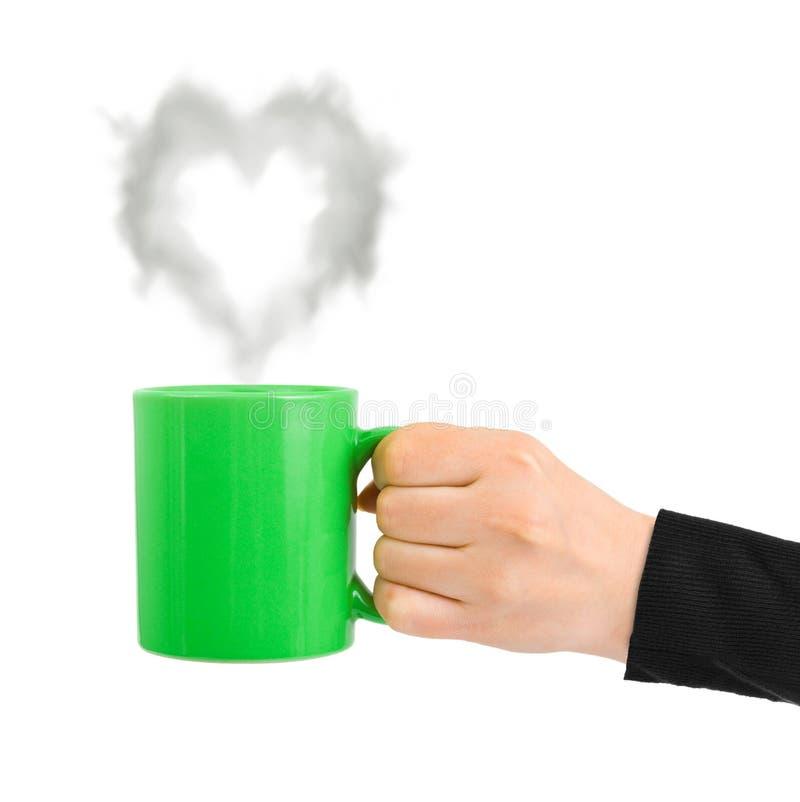 A m?o com copo e o vapor gostam de um cora??o imagem de stock