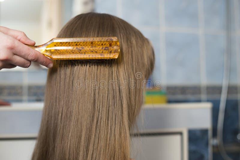 M?o da m?e com a escova que penteia o cabelo justo longo da menina bonito da crian?a ap?s o banho no fundo interior borrado fotos de stock
