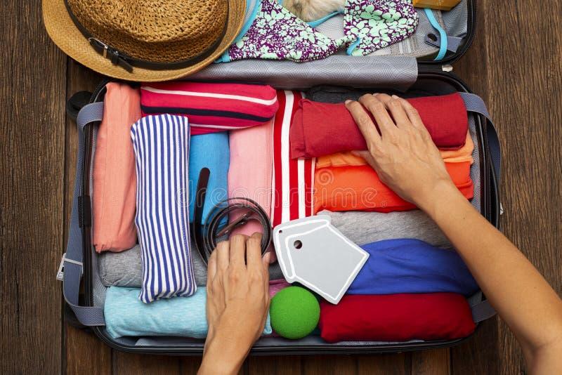 M?o da mulher que embala uma bagagem para uma viagem e um curso novos imagens de stock royalty free