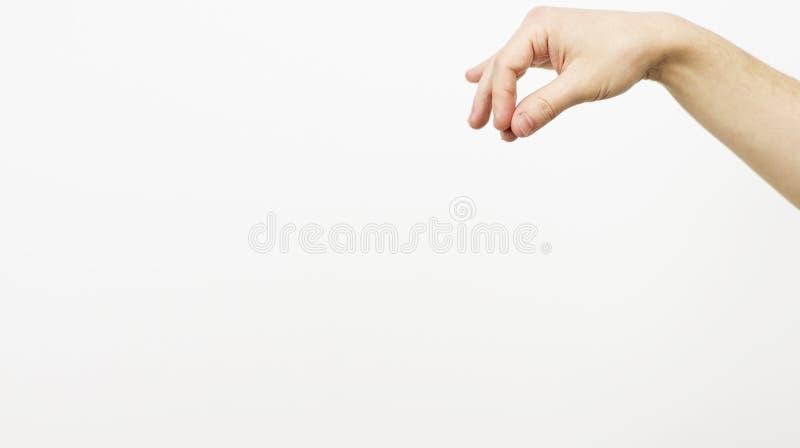 M?o da mulher que guarda algo pouco com dois dedos Isolado com trajeto de grampeamento - m?o de uma f?mea caucasiano para guardar imagens de stock royalty free