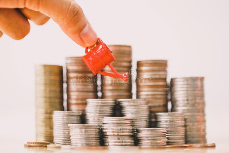 M?o da mulher que guarda a lata molhando vermelha na pilha do dinheiro foto de stock royalty free
