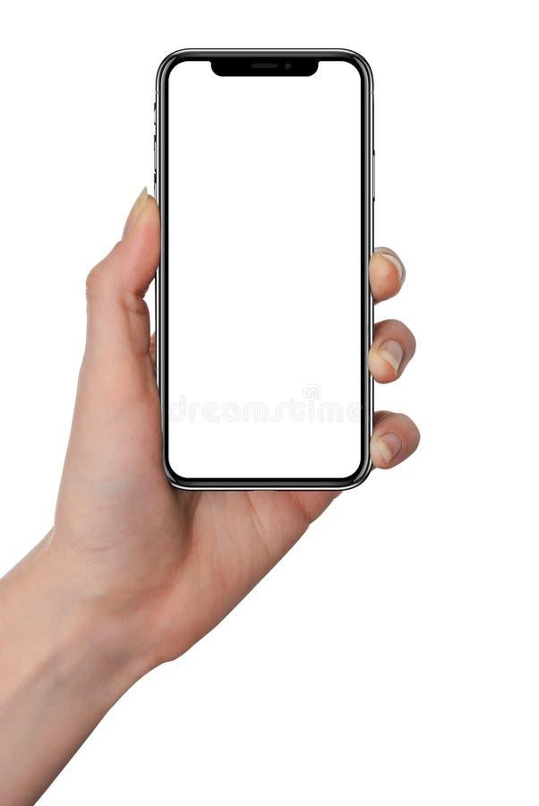 M?o da mulher que guarda o smartphone preto com tela vazia e quadro moderno menos projeto - isolado no fundo branco imagens de stock royalty free
