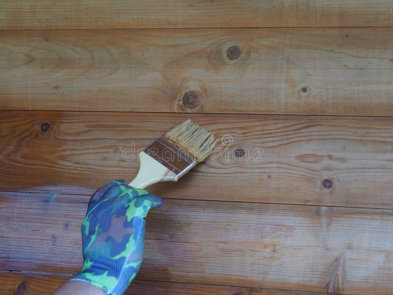 A m?o de um homem com uma escova para pintar uma parede de madeira fotografia de stock