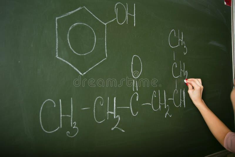 A m?o de um professor da qu?mica est? escrevendo no quadro-negro fotografia de stock