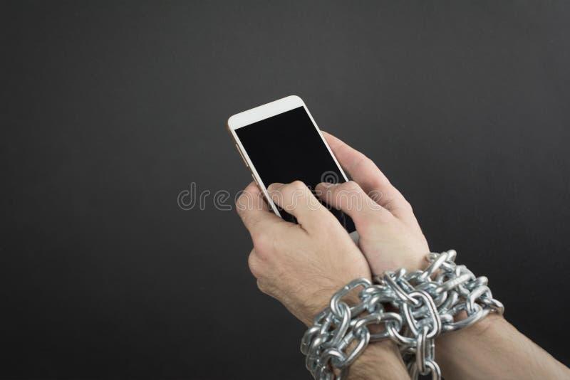 a m?o do homem ? amarrada com uma corrente ao smartphone foto de stock royalty free