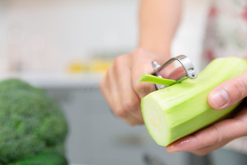 M?o do ` s da mulher que descasca o abobrinha fresco verde Mulher que prepara o alimento delicioso e saudável na cozinha da casa  imagens de stock