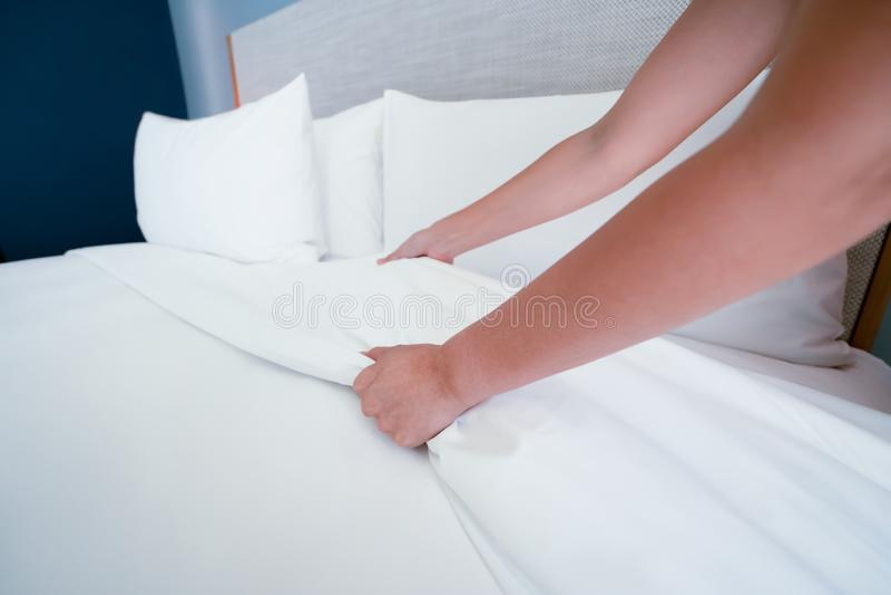 A m?o f?mea estabelece a folha de cama branca no hotel da sala foto de stock royalty free