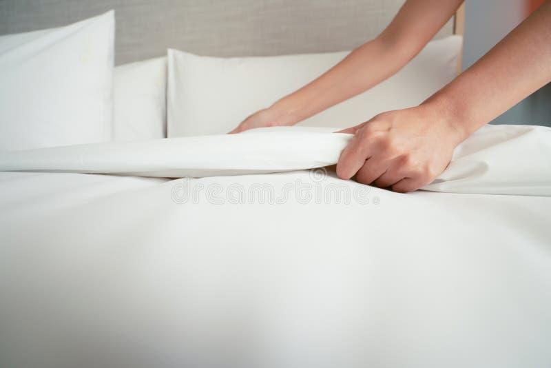 A m?o f?mea estabelece a folha de cama branca no hotel da sala fotografia de stock