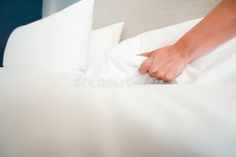 A m?o f?mea estabelece a folha de cama branca no hotel da sala foto de stock
