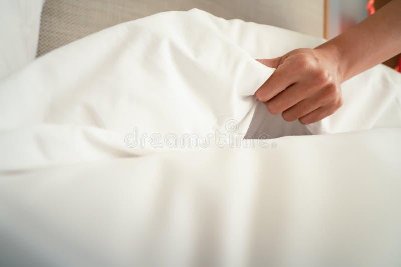A m?o f?mea estabelece a folha de cama branca no hotel da sala imagem de stock