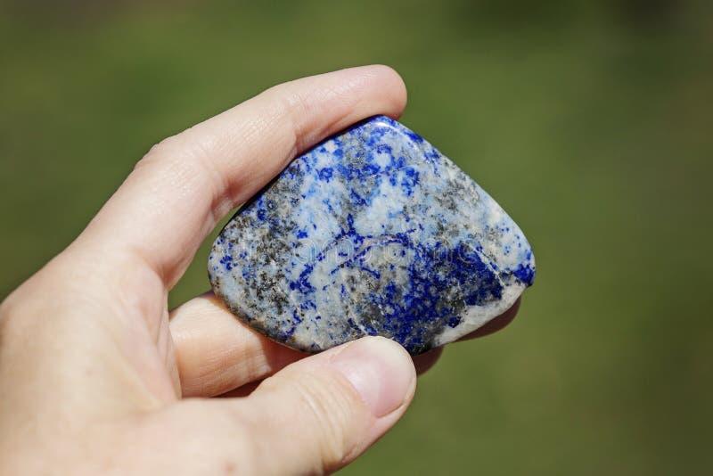 M?o f?mea que guarda a pedra preciosa processada fotos de stock