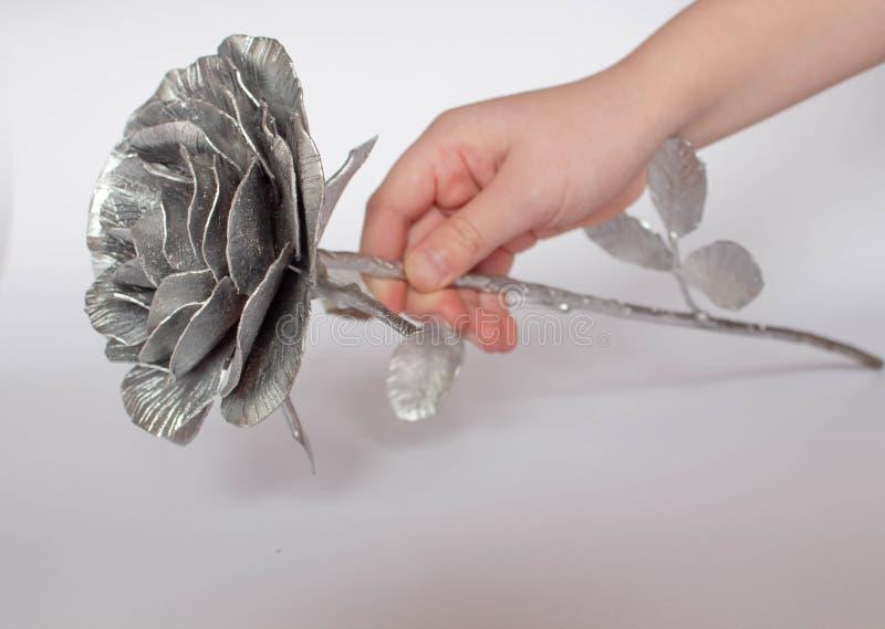 A m?o forjada aumentou Feito a m?o de Rosa forjado do metal em uma parte traseira branca imagens de stock