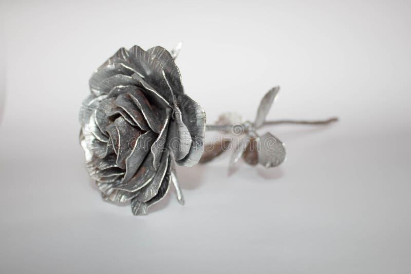 A m?o forjada aumentou Feito a m?o de Rosa forjado do metal em uma parte traseira branca imagens de stock royalty free