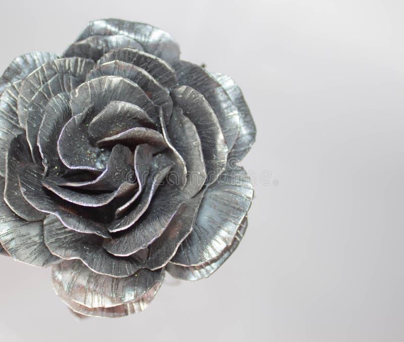 A m?o forjada aumentou Feito a m?o de Rosa forjado do metal em uma parte traseira branca imagem de stock