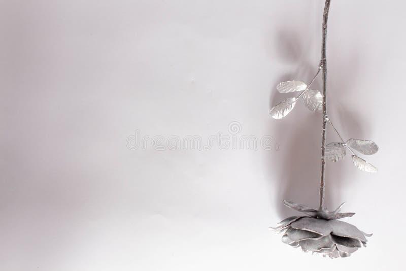 A m?o forjada aumentou Feito a m?o de Rosa forjado do metal em uma parte traseira branca foto de stock