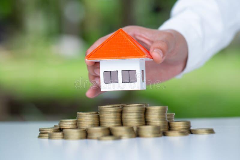 M?o humana que p?e o modelo da casa sobre a pilha das moedas, o dinheiro planejando das economias das moedas para comprar um conc foto de stock