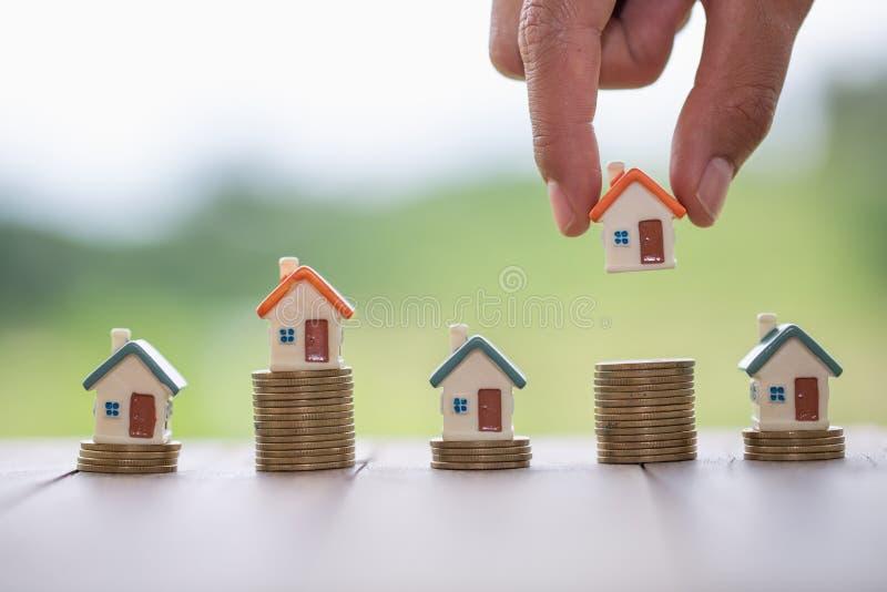 M?o humana que p?e o modelo da casa sobre a pilha das moedas, o dinheiro planejando das economias das moedas para comprar um conc imagem de stock