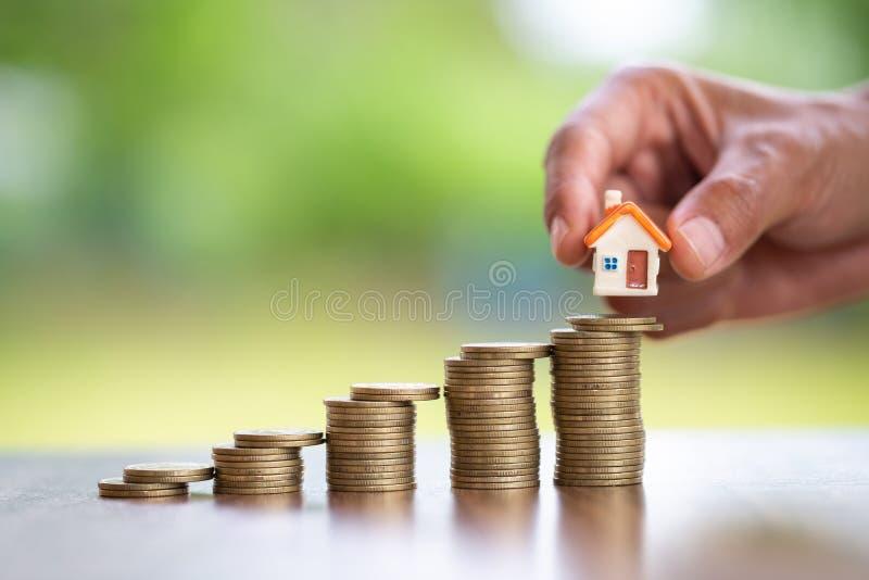 M?o humana que p?e o modelo da casa sobre a pilha das moedas, o dinheiro planejando das economias das moedas para comprar um conc fotografia de stock